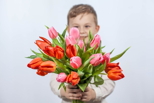 Cute little boy holding a bouquet of flowers. tulips. mothers day. international women's day. portrait of a happy little boy on a white wall. spring.