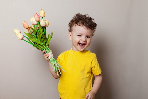 Cute little boy holding a bouquet of flowers. tulips. mothers day.