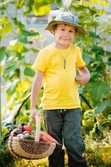 Cute little boy holding a bunch of fresh organic vegetables in domestic garden.