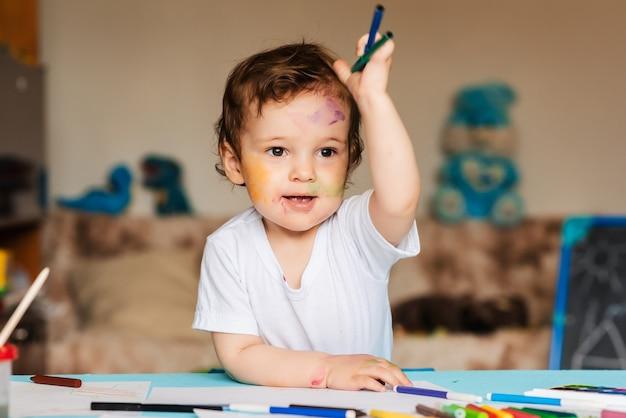 Милый маленький мальчик держит цветные карандаши и маркеры