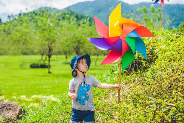 Cute little boy holding a colorful pinwheel