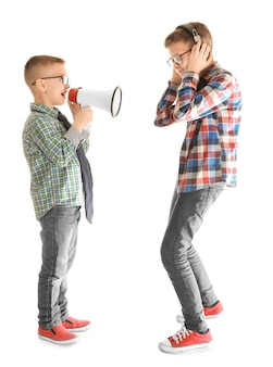 Cute little boy ignoring his friend with megaphone, on white