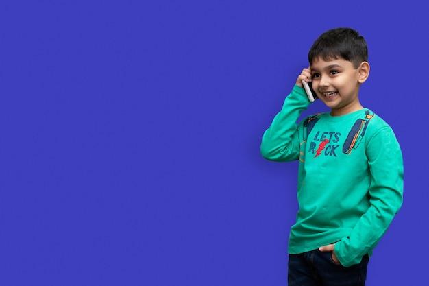 녹색 셔츠를 입은 귀여운 소년은 복사 공간이 있는 일반 배경에서 전화 통화를 합니다.