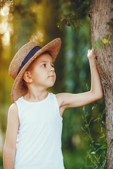 帽子のかわいい男の子は夏の公園で時間を過ごす