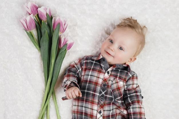 格子縞のシャツを着たかわいい男の子がピンクのチューリップの花束を保持しています。