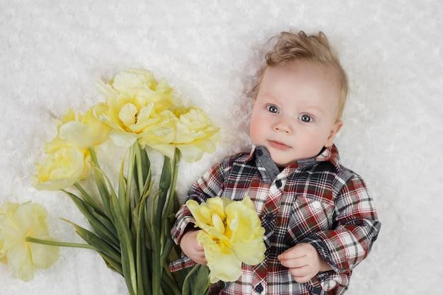 格子縞のシャツを着たかわいい男の子が黄色のチューリップの花束を保持しています。