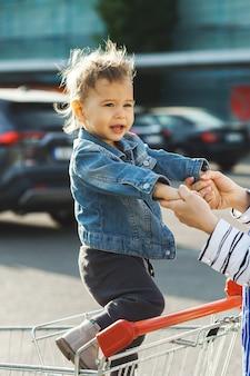 Милый маленький мальчик в корзине покупок