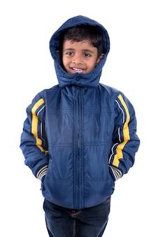 白い背景で隔離の冬のコートのかわいい男の子
