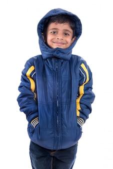 白いスペースに分離された冬のコートでかわいい男の子