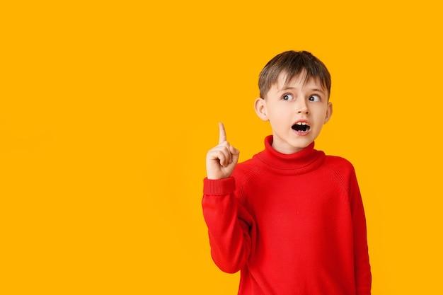 色の背景に何かを指している秋の服を着たかわいい男の子