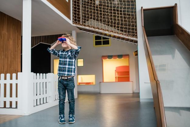 スライドの背景の遊び場に立っている間双眼鏡を通して見ているカジュアルウェアのかわいい男の子