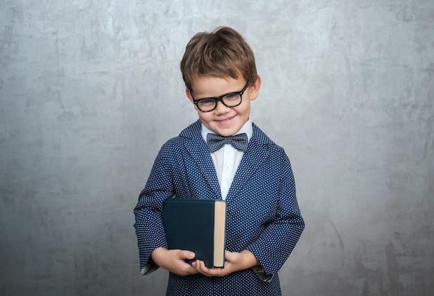 어두운 안경에 귀여운 어린 소년, 나비가 달린 세련된 재킷과 그의 손에 책