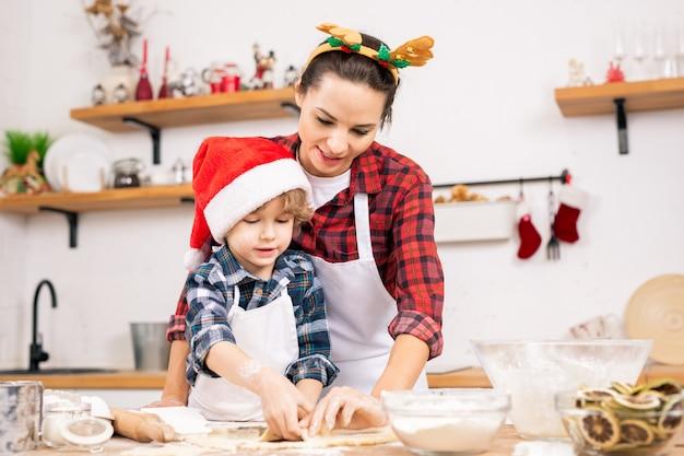 Милый маленький мальчик в шапке санта-клауса и его мать в рождественской повязке на голову делают имбирные пряники на кухне