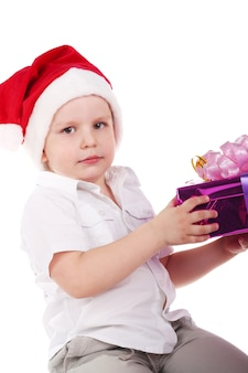선물을 들고 산타클로스 모자를 쓴 귀여운 소년