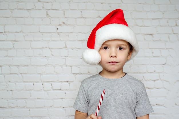 白いレンガの壁の背景にクリスマスキャンディケインのお菓子を食べるサンタ帽子のかわいい男の子