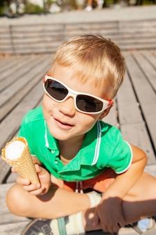 夏の公園で休んでいる間おいしいアイスクリームコーンを食べて、面白いしかめっ面を作るスタイリッシュなサングラスのかわいい男の子