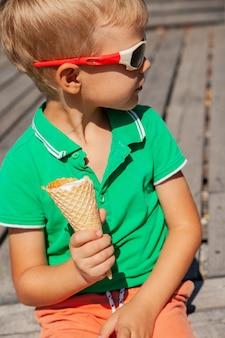 おいしいバニラアイスクリームコーンを食べて、公園で夏を楽しんでいるスタイリッシュなサングラスのかわいい男の子