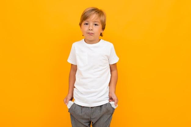 Tシャツとズボンのかわいい男の子は、黄色の背景で隔離のポケットに手を保持します。