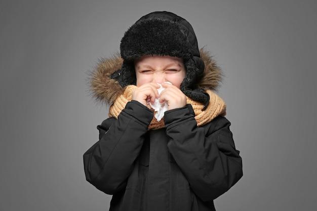灰色の背景に彼の鼻を吹くためにティッシュを使用して暖かい服を着たかわいい男の子