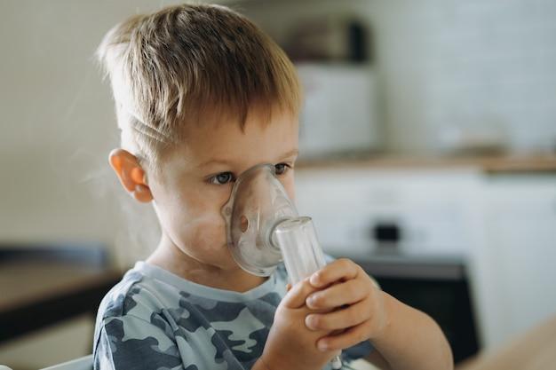 Милый маленький мальчик вдыхает небулайзер