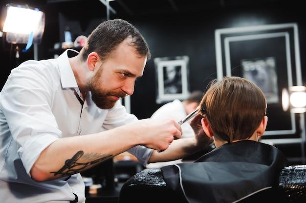 Милый маленький мальчик получает стрижка в парикмахерской.