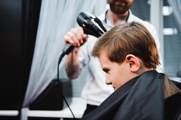 かわいい男の子は理髪店で美容院で散髪されています。