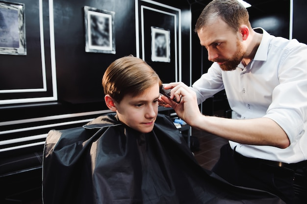 Cute little boy is getting haircut by hairdresser at the barbershop.