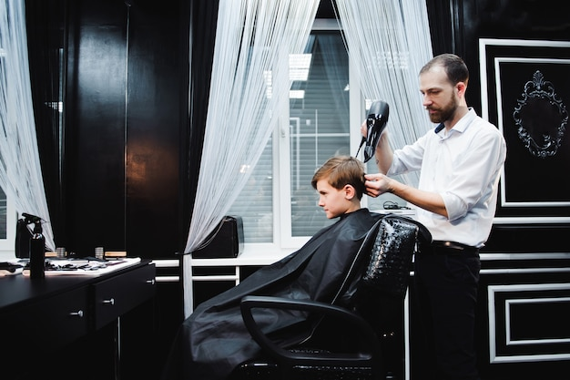 Cute little boy is getting haircut by hairdresser