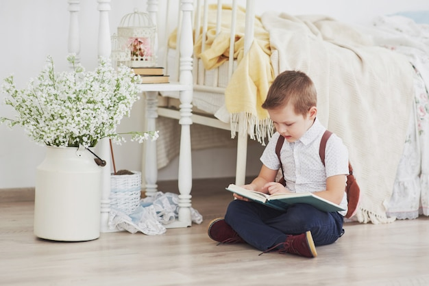 Cute little boy is going to school for the first time. child with bag and book. kid makes a briefcase, child room on a background
