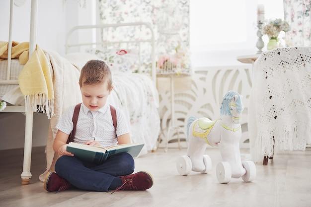 かわいい男の子は初めて学校に行きます。ランドセルと本を持つ子供。子供はブリーフケース、子供部屋を作ります。学校に戻る