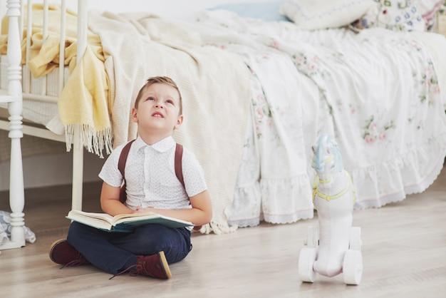 かわいい男の子は初めて学校に行きます。ランドセルと本を持つ子供。子供は、背景にブリーフケース、子供部屋を作ります。学校に戻る