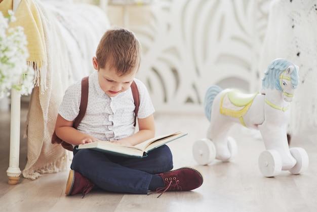 かわいい男の子は初めて学校に行きます。ランドセルと本を持つ子供。子供はブリーフケース、子供部屋を作ります