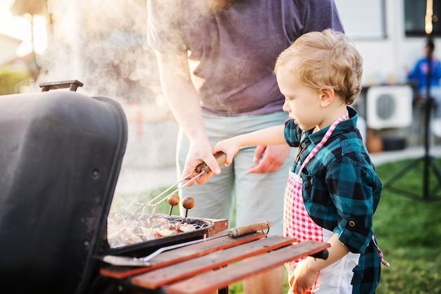 Милый маленький мальчик держит фартук и научиться делать барбекю с помощью родителей.