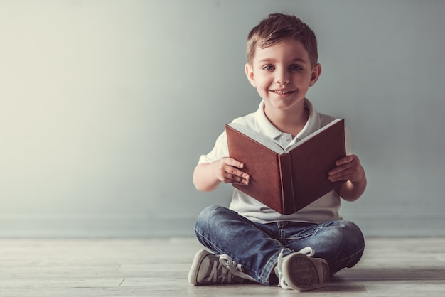 Cute little boy is holding a book, looking at camera.