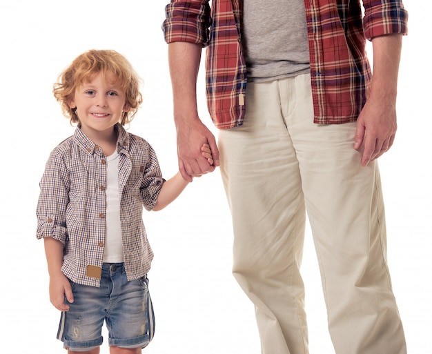 Cute little boy is holding his grandpa hand.
