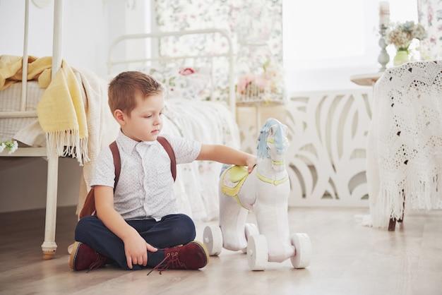 かわいい男の子はおもちゃの馬で遊んでいます