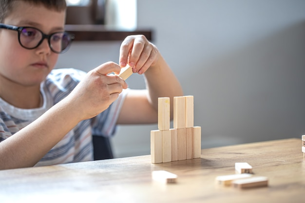 A cute little boy is playing a board game with wooden cubes and a turret.