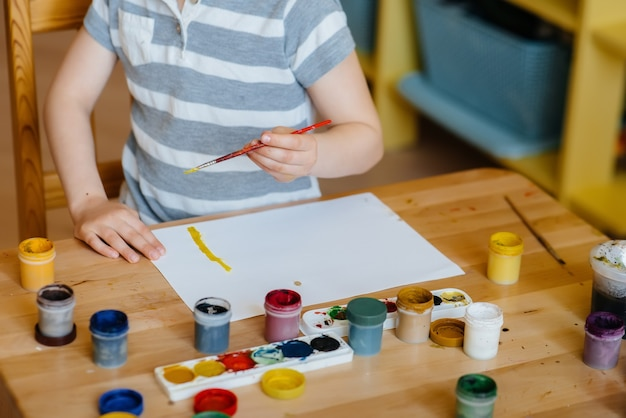 A cute little boy is playing and painting in his room. recreation and entertainment. stay at home.