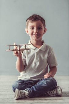 Cute little boy is playing with toy plane, looking at camera
