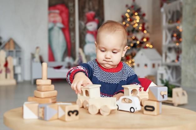 귀여운 꼬마 장난감 나무 기차, 장난감 자동차, 피라미드와 큐브, 학습 개발 개념으로 놀고있다. 어린이 미세 운동 기술, 상상력 및 논리적 사고의 개발