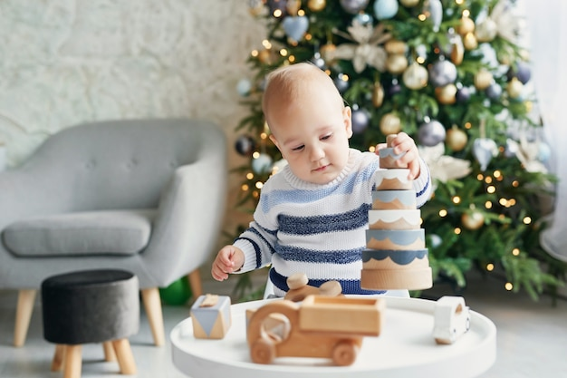Cute little boy is playing with toy wooden train, toy car, pyramid and cubes, learning development concept. development of kids fine motor skills, imagination and logical thinking