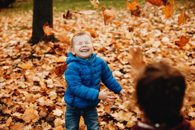 お母さんと一緒に公園の葉っぱで遊んで笑って楽しんでいるかわいい男の子。