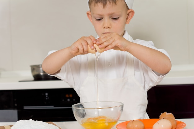 Cute little boy learning to bake a cake standing breaking eggs into a bowl at a kitchen counter