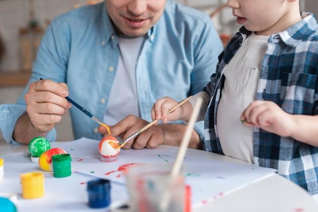 Милый маленький мальчик учится рисовать яйца на пасху