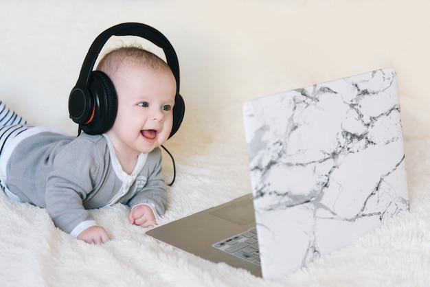 かわいい男の子はヘッドフォンで彼の胃にあり、ラップトップ、セレクティブフォーカスに見えます