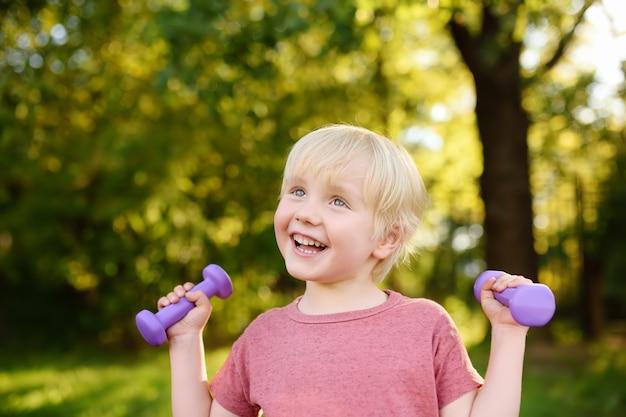 Cute little boy lifting dumbbells outdoors