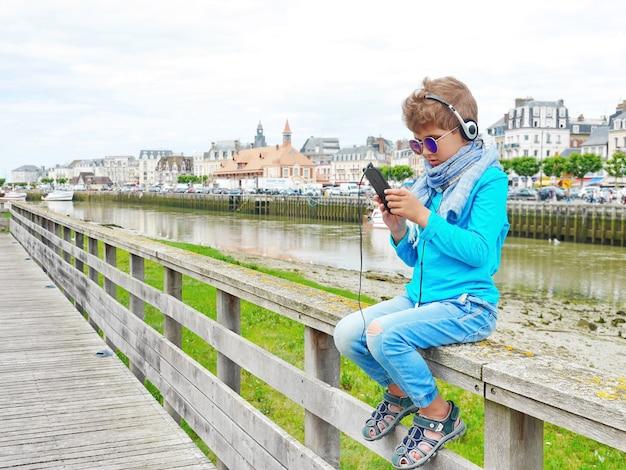 Милый маленький мальчик слушает музыку в наушниках. он любит музыку. он сидит на мосту с рекой и крышами вокруг него