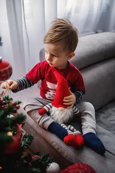 装飾に触れるクリスマスツリーを見ているかわいい男の子。少年は小さな小人を抱いています。明けましておめでとうございます。