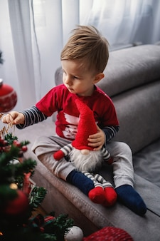 Cute little boy looking at christmas tree touching decoration. boy is hugging little dwarf. happy new year.