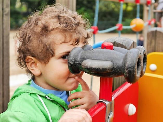 遊び場で双眼鏡を通して見ているかわいい男の子